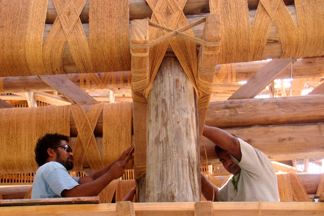 Samoan workers fasten beam structures of the fale.