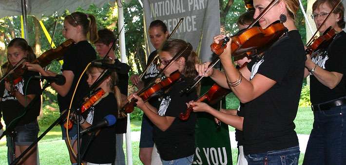 Photo of a group of fiddlers on stage