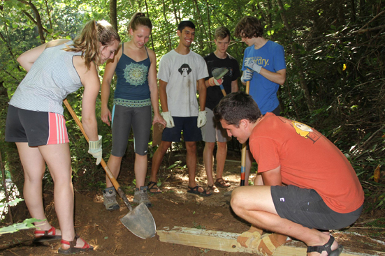 group working on a waterbar on trail