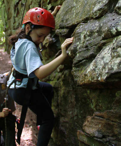 Little girl maneuvering on rock wall learning how to climb