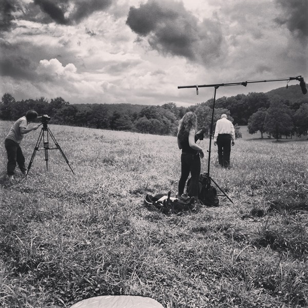 filming crew standing in field with old man doing interview