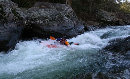 paddler traversing the whitewater rapid