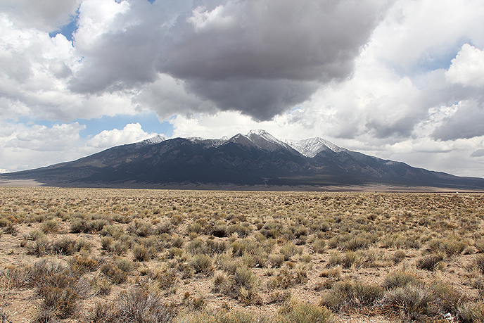 desert shrubbery in the foreground, mountain peaks in background, with white and dark clouds