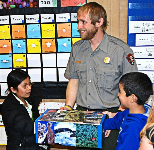 A ranger smiles as students reach into a box filled with natural items.