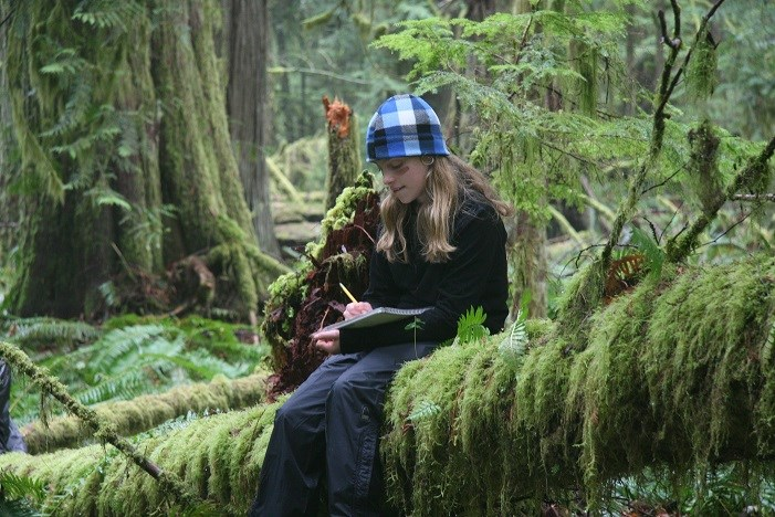 A girl writes in her journal while sitting on a log in a lush, green forest.