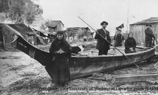 Historic photo of the Hicks family standing in and around a dugout canoe