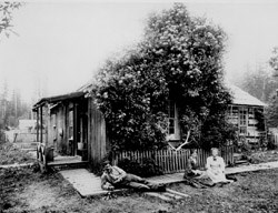 Historic photo of two women and a man outside of a homestead on Lake Ozette