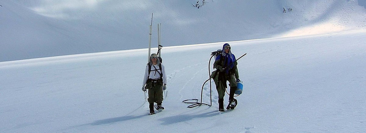 Two researchers snowshoeing