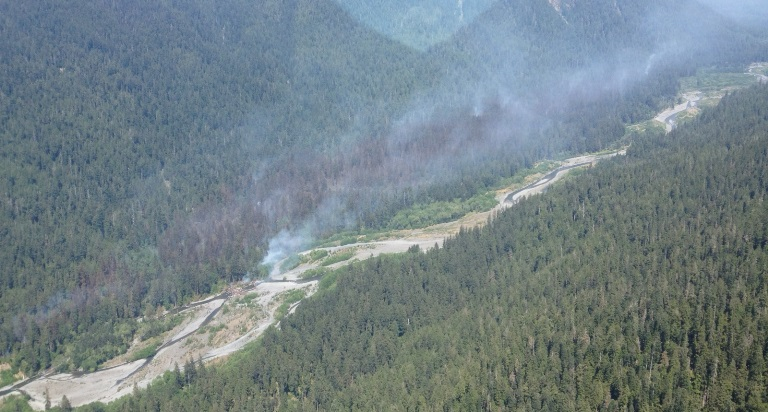 Ariel view of smoke rising from the forest along the edge of Queets River.