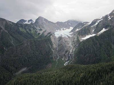 White Glacier recedes up the rocky Olympic mountains, with towering jagged peaks above and leaving waterfalls that drain into a lush green valley below.