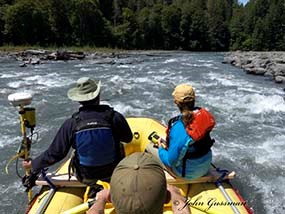Two member of the inter-agency sediment team survey the Elwha River from a raft.