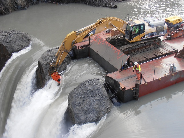 barge with excavator mounted on it next to a dam