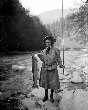 Historic image of a woman holding a large salmon near a river.