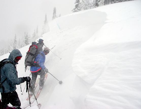 three people standing on snow-covered slope, studying recent avalanche