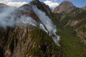 Smoke billows from the Constance Fire as it burns across a mountainside