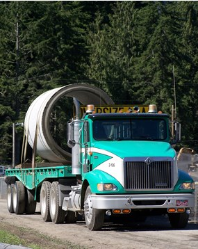 turquoise flatbed truck carrying large concrete cylinder