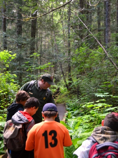 Park Ranger and young students observing plants on a forest trail.
