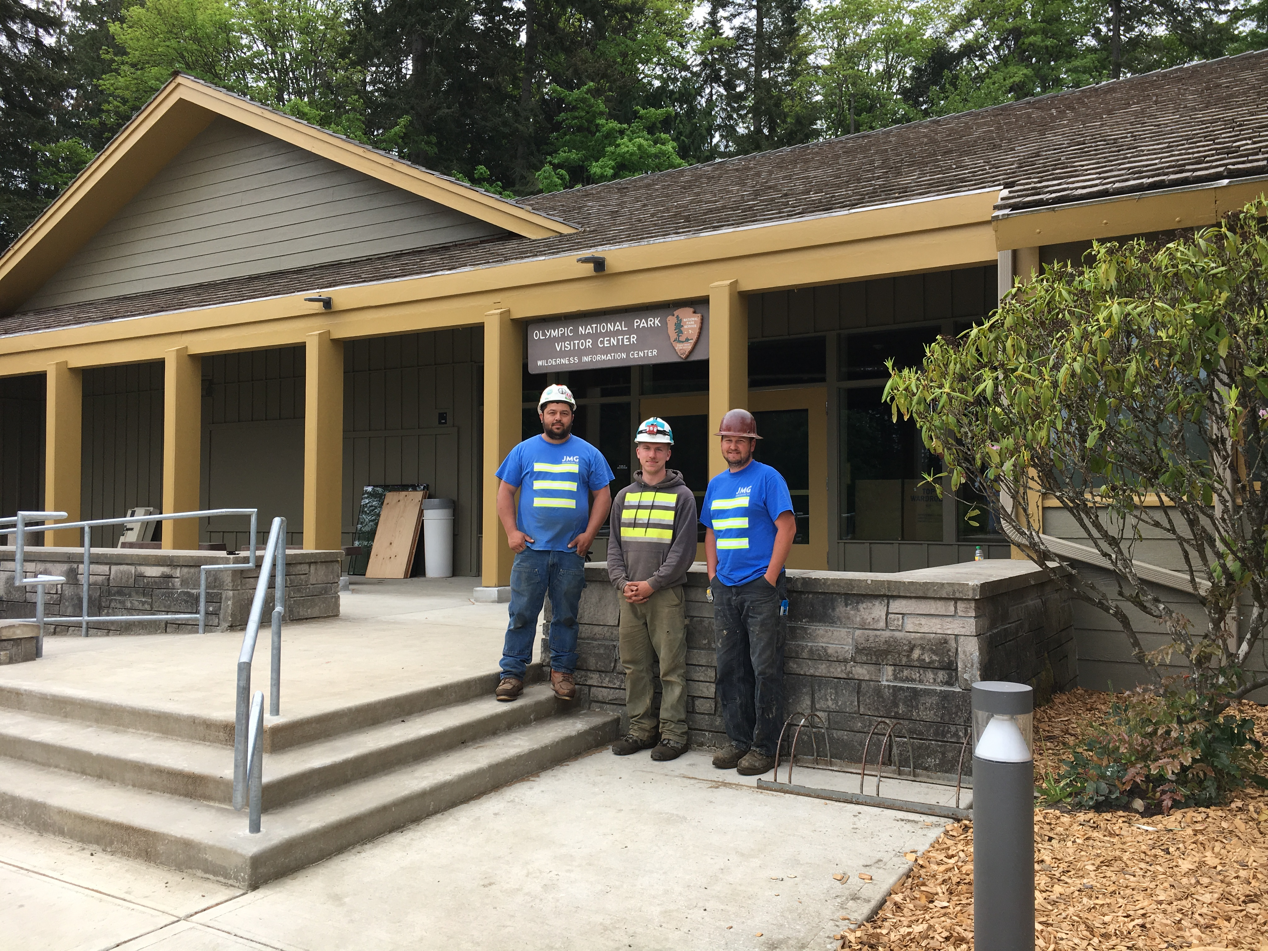Construction workers standing in front of renovated visitor center