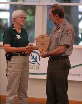 man in National Park Service uniform handing wooden arrowhead to woman wearing green polo shirt and khaki pants