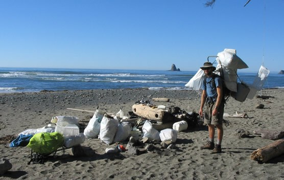 man with backpack standing near many filled garbage bags on ocean beach