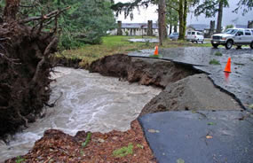 road damaged by rushing creek waters