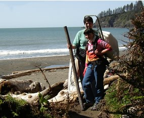 two people with trash bags with ocean in background