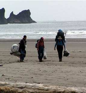 three people carrying large bundles on sandy beach