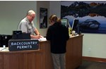 man helps woman at information desk