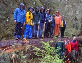 eleven people, all dressed in raingear, standing on and beside large fallen tree