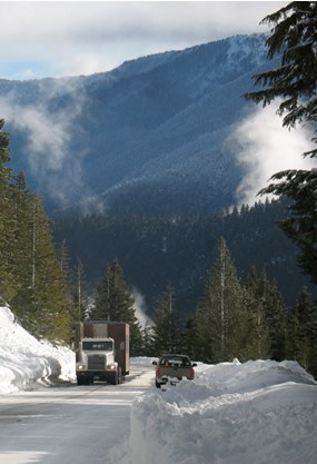 large trailer being pulled up snow-covered road by truck