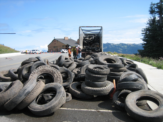 large pile of tires in a parking lot with truck in background