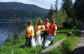 four women in reflective vests beside a lake