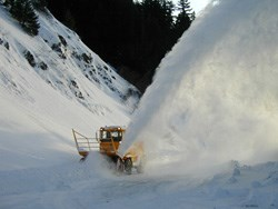 Snowplows blow snow off of roadway.