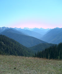 A view of sky mountains from atop a mountain meadow during the summer