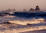 ocean waves with rocky islands in background