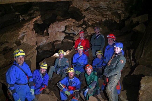Several rangers in off trail gear in the cave.