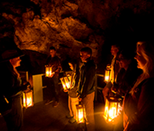 A tour group participating in a Candlelight Cave Tour.