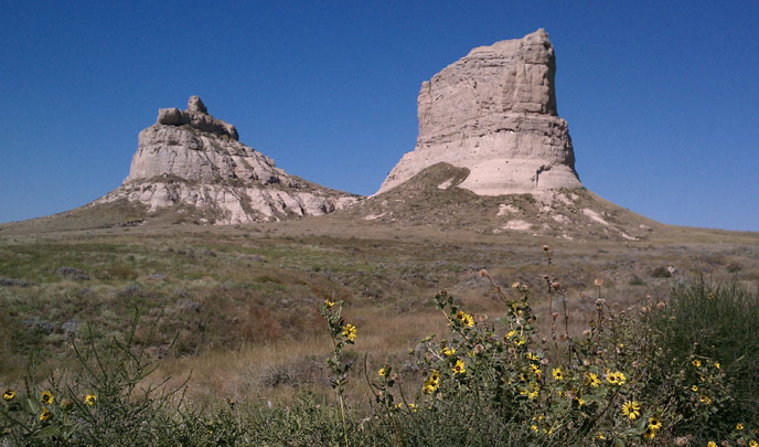 Two large tan rock pillars stand out of a green landscape with sunflowers in the foreground.
