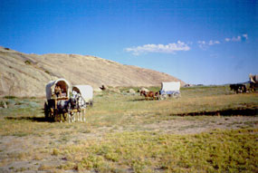 Photo image of Independence Rock and emigrant wagons.