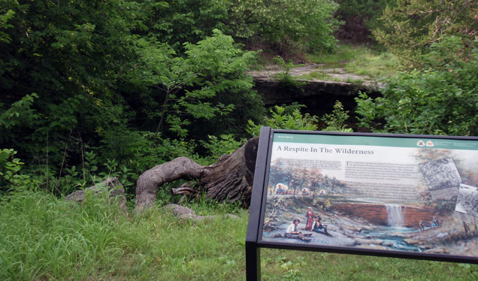A wayside exhibit with an illustration of a waterfall stands in front of a rock shelf surrounded by green vegetation.