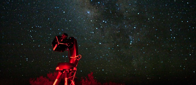 A large camera on a tripod points up at a starry night sky.