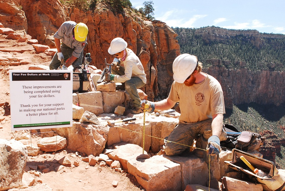 Three employees or volunteers working on a section of trail in the Grand Canyon