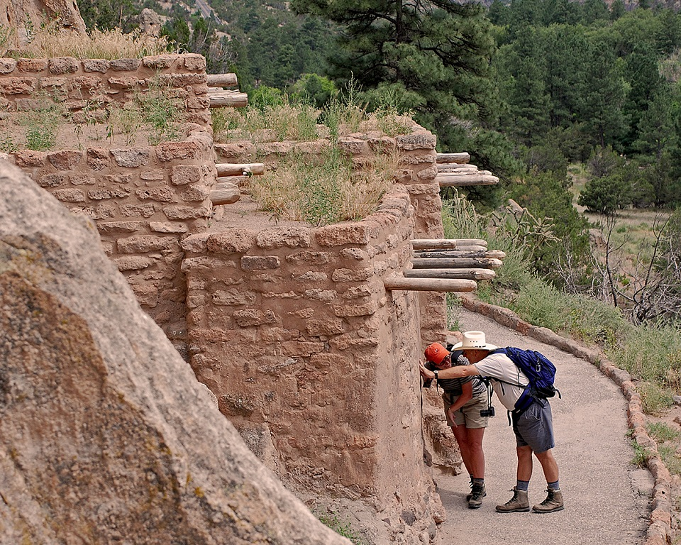 Two visitors peering inside a Pueblo structure