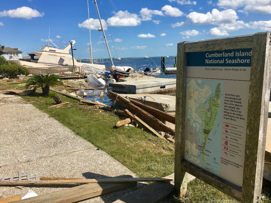 park sign, debris, and a boat along the seashore