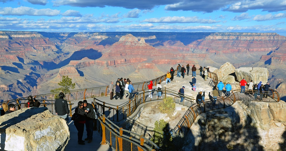 Groups of visitors at an overlook over the Grand Canyon