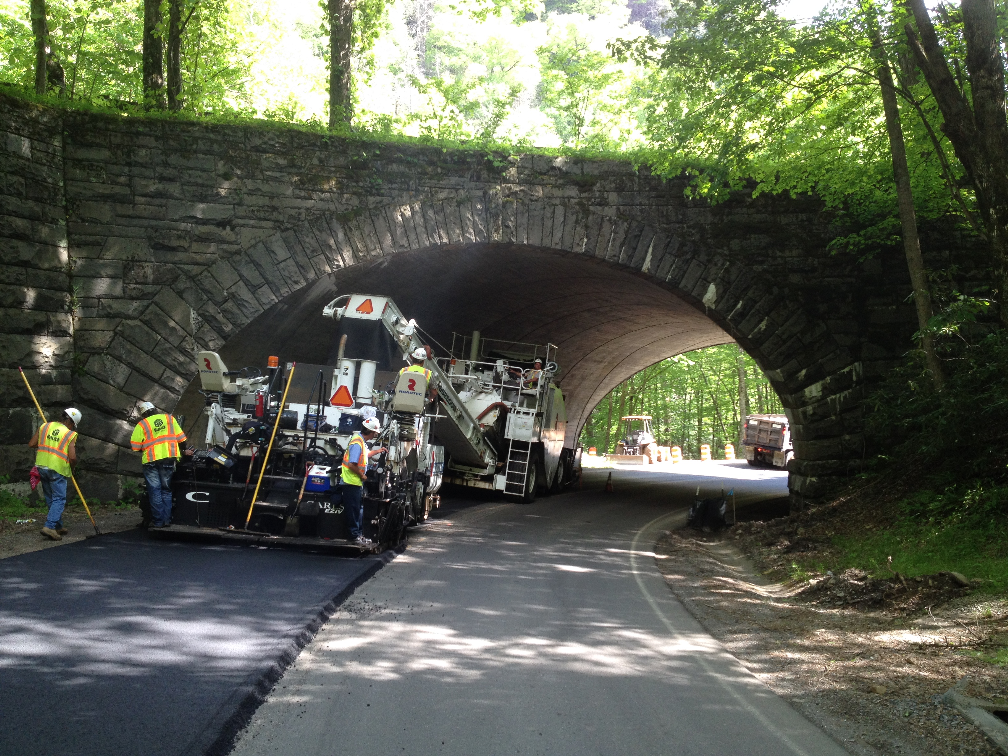 Road crew paves a road just before a stone bridge overpass.