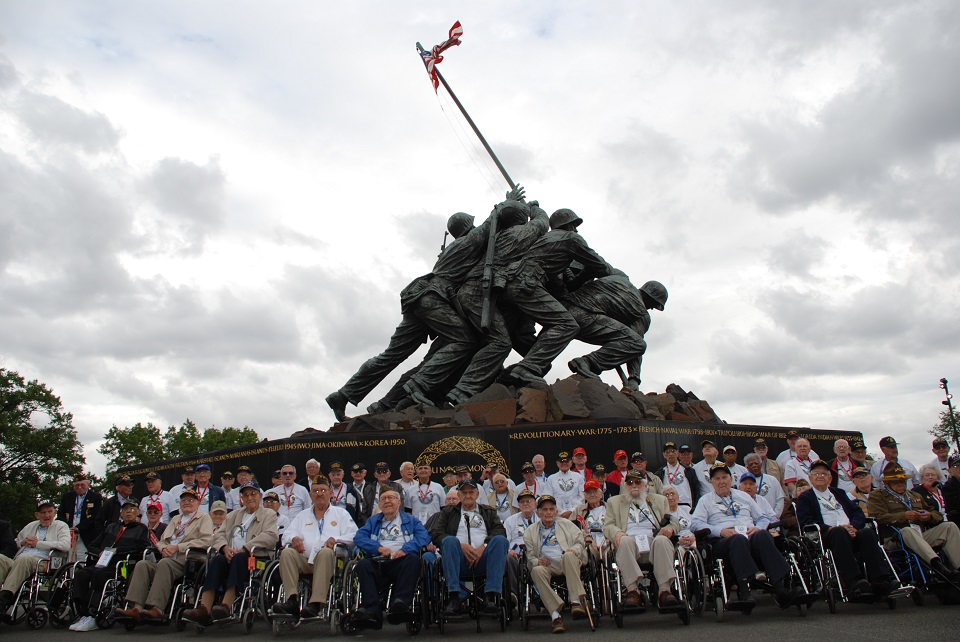 A group of veterans in front of the U.S. Marine Corps War Memorial statue
