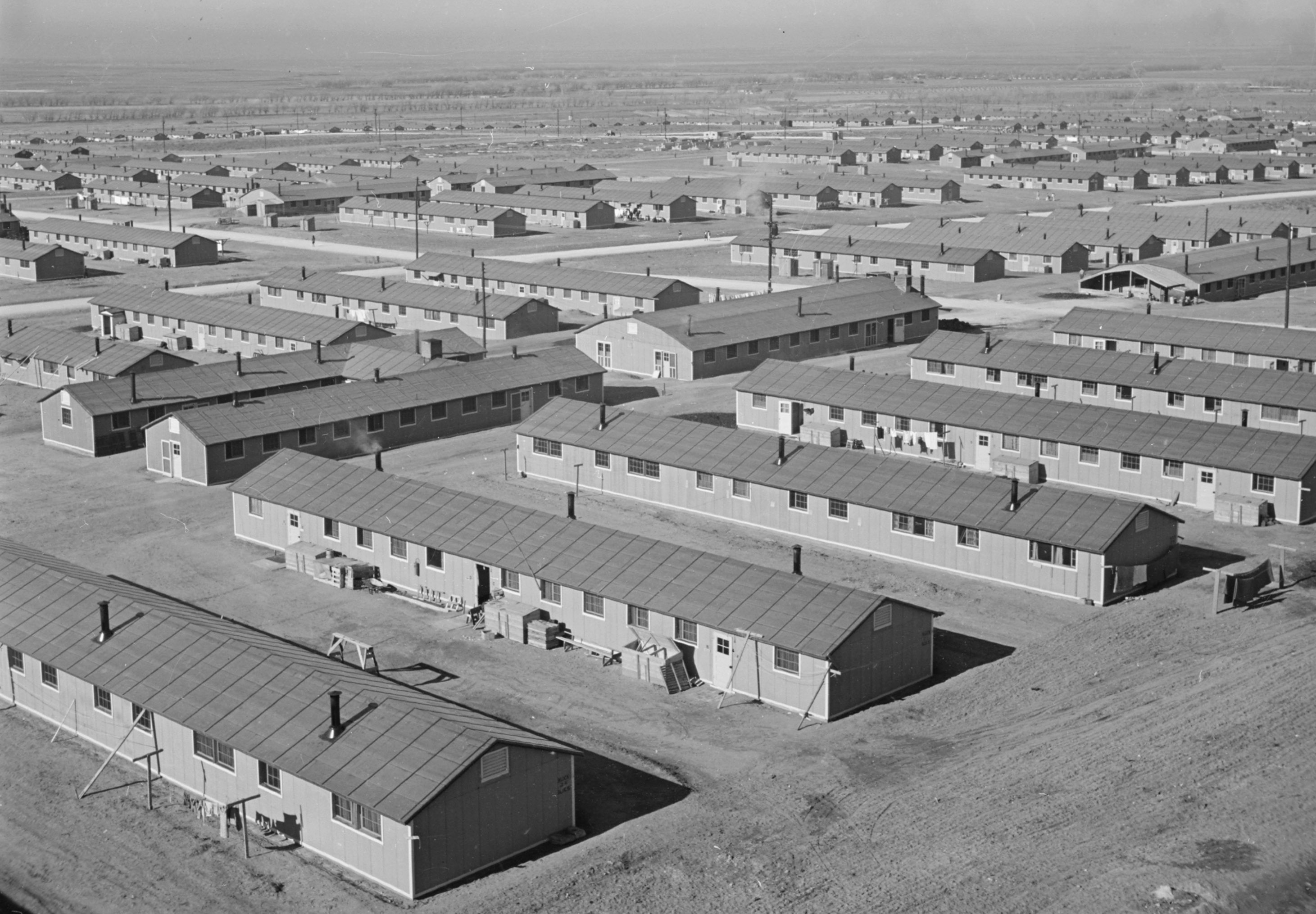 Black and white photo of rows and rows of low, bare, one-story buildings.