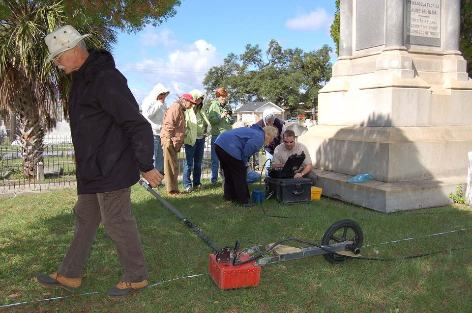 Man pulling a ground penetrating radar near a monument while other view the results on a computer