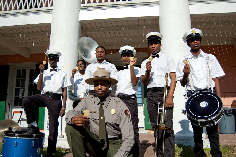 Park ranger and youth brass band holding up junior ranger badges